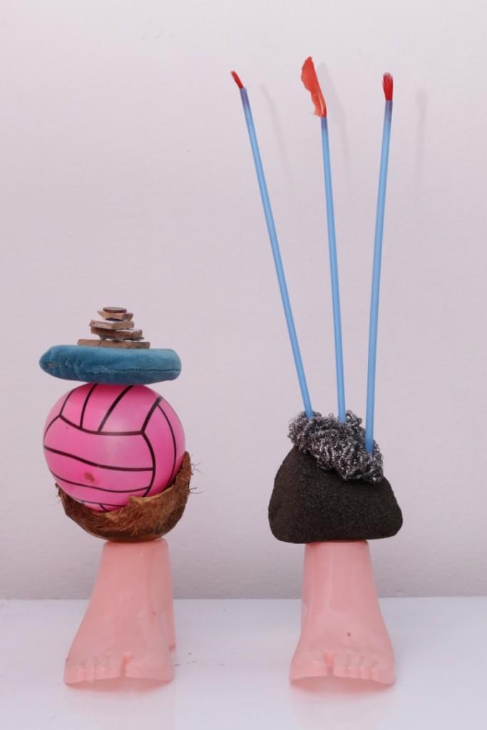 Détails de l'installation, deux pieds en plastique, une noix de coco, des fragments de carrelage, une pièce de monnaie, une pierre volcanique, une éponge argenté, trois pailles, trois plumes de coq rouge